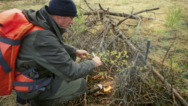 male wilderness survival expert sharpening a stick by the fire on a forest clearing - survival stock videos & royalty-free footage