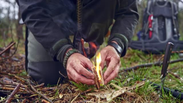 männliche wildnis überleben experte starrt ein feuer, um lager im wald zu errichten - überleben stock-videos und b-roll-filmmaterial