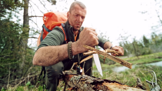 slo mo male wilderness survival expert using his knife to make kindling in the wilderness - 40 44 years stock videos & royalty-free footage