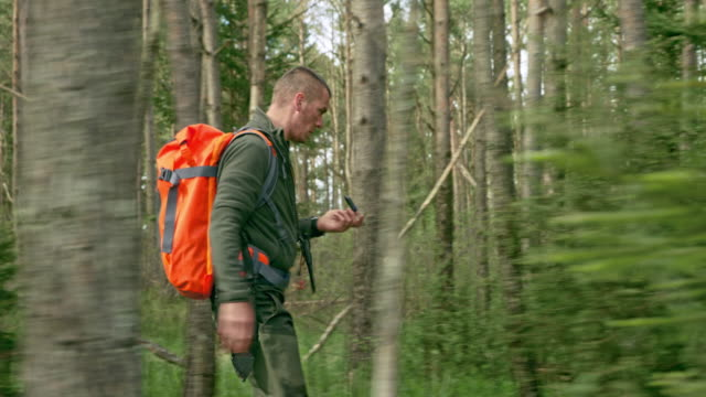 ts male wilderness survival expert walking in the woods using a compass - survival stock videos & royalty-free footage