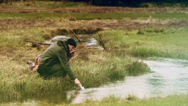 vidéos et rushes de expert masculin de survie sauvage lavant son couteau dans la rivière - survie