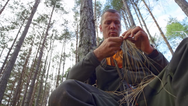 male wilderness survival expert weaving with dried grass in the woods - survival stock videos & royalty-free footage