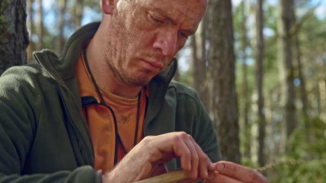 männliche wildnis überleben spezialist weben getrocknete grashalme im wald - überleben stock-videos und b-roll-filmmaterial