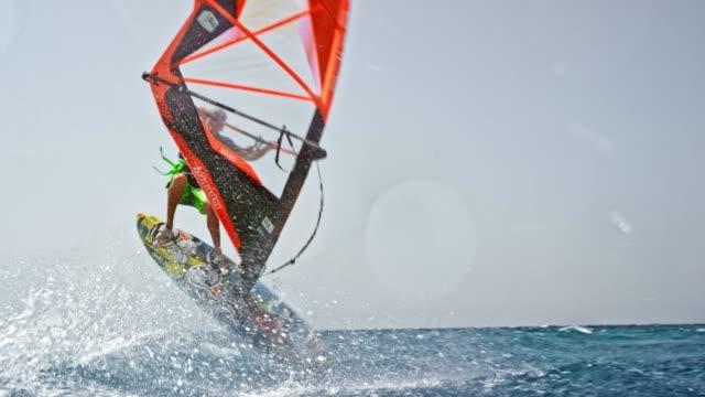 stockvideo's en b-roll-footage met slo mo mannelijke windsurfer doen van een flip met zijn windsurf in zon - windsurfen
