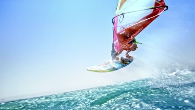 slo mo male windsurfer doing a jump in sunshine - risk stock videos & royalty-free footage
