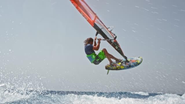 slo mo männlichen windsurfer machen einen sprung in der luft bei sonnenschein - stunt stock-videos und b-roll-filmmaterial