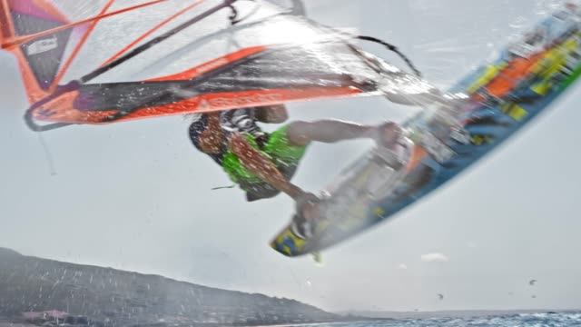 SLO MO Male windsurfer jumping off the wave and into the air in sunshine
