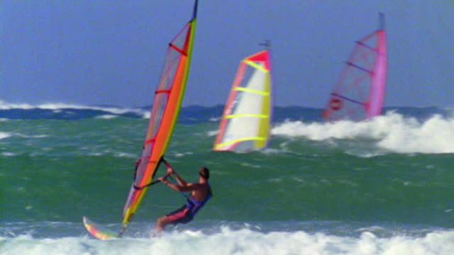 pan male windsurfer jumping off wave, doing flip in air + wiping out / others in background / hawaii - 失敗点の映像素材/bロール