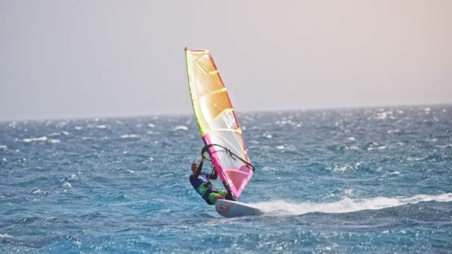 SLO MO Male windsurfer riding in windy conditions on a sunny day