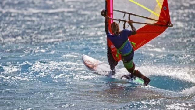 stockvideo's en b-roll-footage met slo mo mannelijke windsurfer paardrijden de golven in de zon - windsurfen