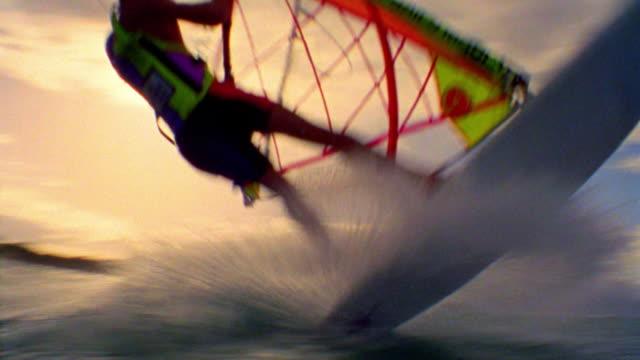 PAN male windsurfer speeding past camera + jumping into air / Hawaii