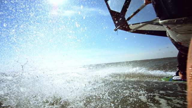 Male windsurfing trick, hand spash