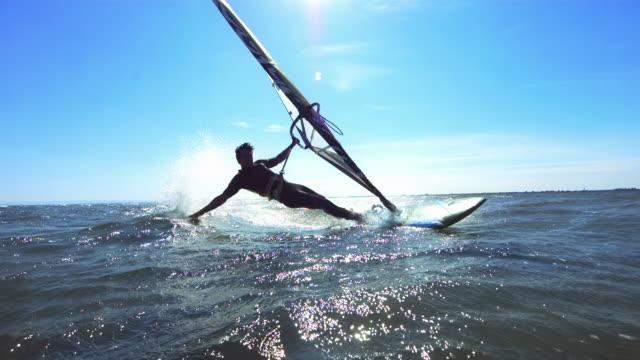 Male windsurfing trick, hand splash