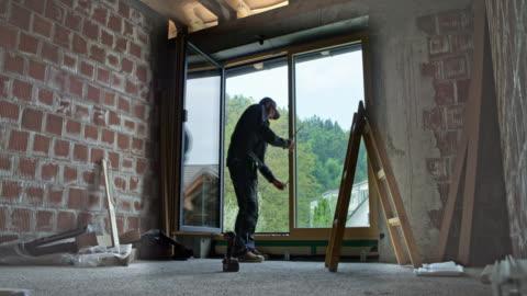 vídeos y material grabado en eventos de stock de trabajador varón ld ajuste la puerta del balcón después de la instalación - típico de la clase trabajadora