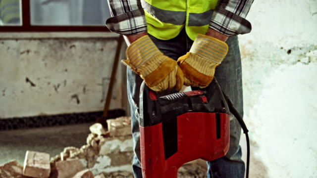 male worker holding a jackhammer and breaking the concrete floor - forza video stock e b–roll