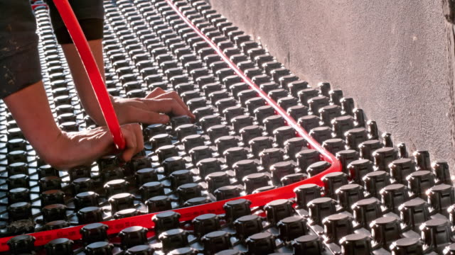 LD Male worker inserting red pipes into the castellated panels for floor heating