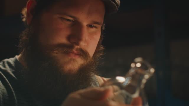 männlicher arbeiter inspiziert glasbehälter in der industrie - flasche stock-videos und b-roll-filmmaterial