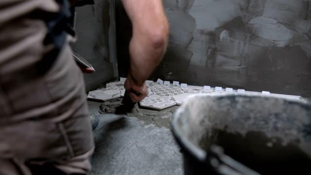 vidéos et rushes de travailleur de sexe masculin poser des carreaux sur le sol de la salle de bain - céramique