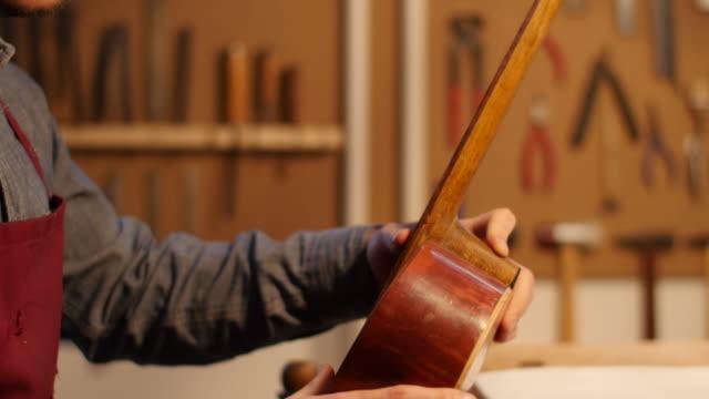 Male worker making guitar in workshop