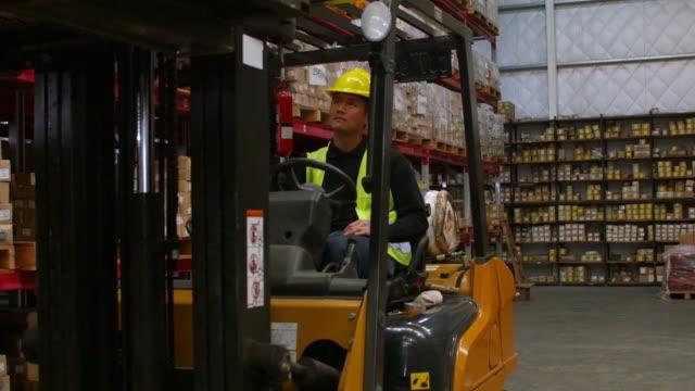 vidéos et rushes de homme travailleur opérer chariot élévateur en entrepôt - faire fonctionner