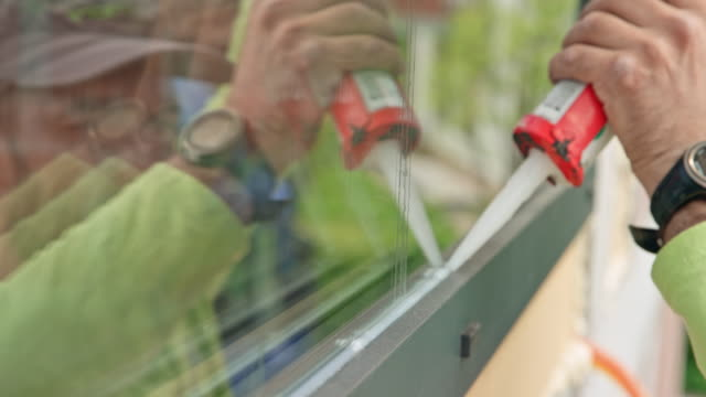 male worker placing silicone on the glass window - glue stock videos and b-roll footage