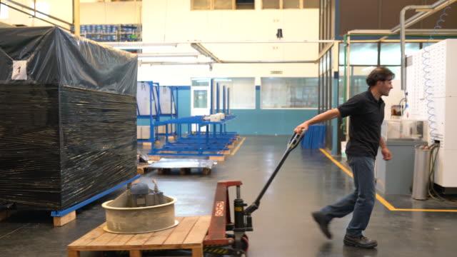 vidéos et rushes de matériel de traction de travail masculin sur la prise de palette dans l'usine - ouvrier