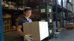 Male worker standing with a box in warehouse