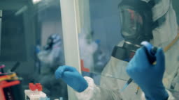 Male worker uses pipette while developing a vaccine in laboratory.