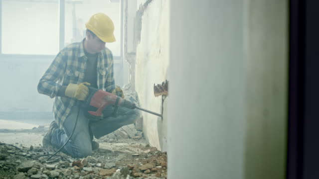 ds male worker using a jackhammer to make holes in a wall for the pipes - pneumatic drill stock videos & royalty-free footage