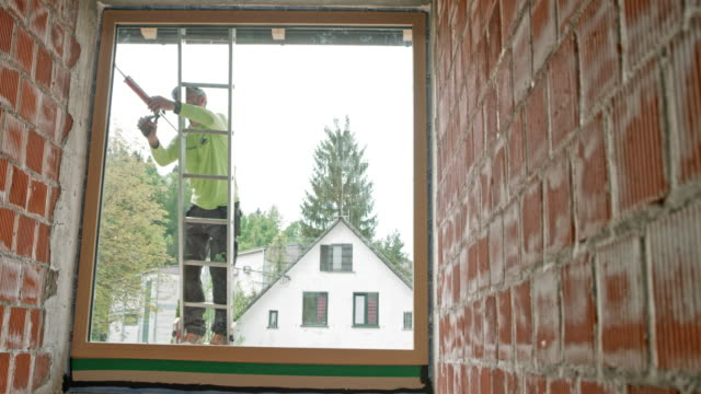 male worker using a silicone gun on the glass window while standing on the ladder outside - ladder stock videos & royalty-free footage