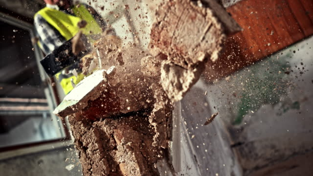 SLO MO Male worker using a sledge hammer to break a wall