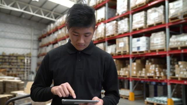 デジタル タブレットを使用してウェアハウス内男性労働者 - 流通センター点の映像素材/bロール