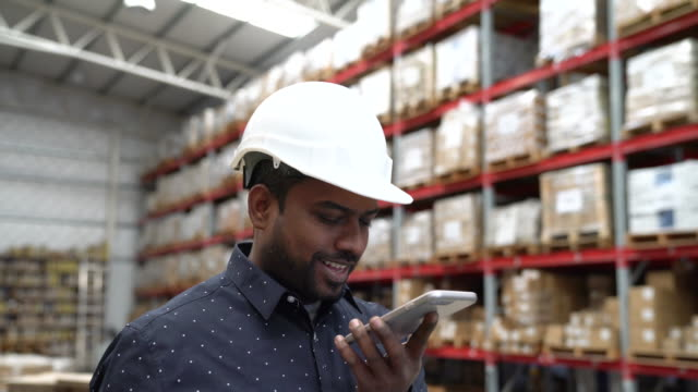 male worker using smart phone in warehouse - conference phone stock videos & royalty-free footage