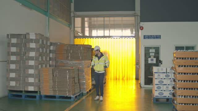 male worker wearing safety uniform checking inventory of beverage product in a bottling factory - non us film location stock videos & royalty-free footage