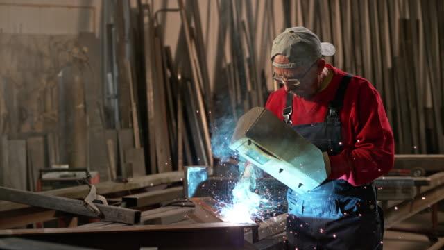 SLO MO DS Male worker welding a piece of metal