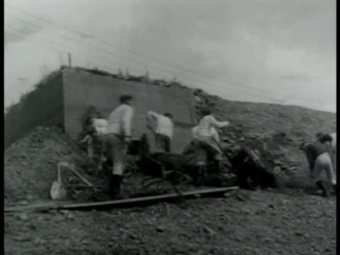 Male workers shoring up exterior wall of bunker w/ wheel barrows of dirt German Nazi officer in structure using binoculars mounted on tripod