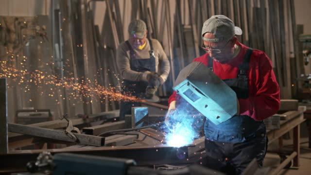 slo mo ld male workers welding in the workshop - 鉄点の映像素材/bロール