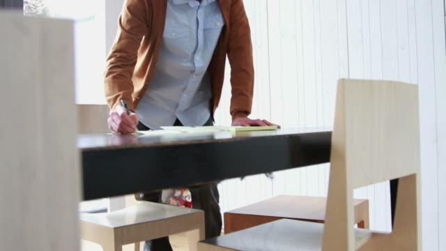 vidéos et rushes de homme travaillant de la maison faire des remarques - hot desking