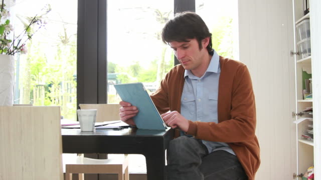 Male working from home on digital tablet