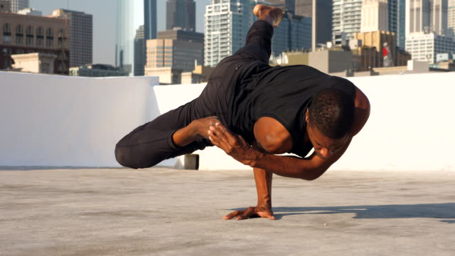 ms male yogi balancing on one hand while on rooftop overlooking city skyline - tights stock videos & royalty-free footage