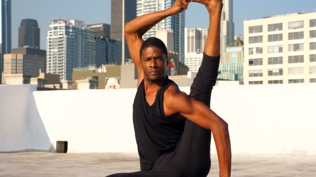 ms male yogi seated on rooftop overlooking city with one leg over head - tights stock videos & royalty-free footage