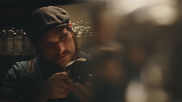 vidéos et rushes de le jeune propriétaire mâle examine la bouteille à l'usine - manufacturing occupation