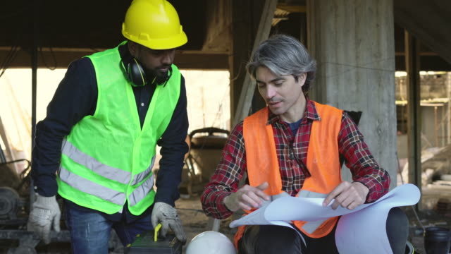 males coworkers discussing over blueprint at site - hard hat stock videos & royalty-free footage