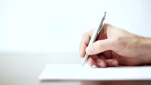 vidéos et rushes de homme de main écrit dans les documents - stylo