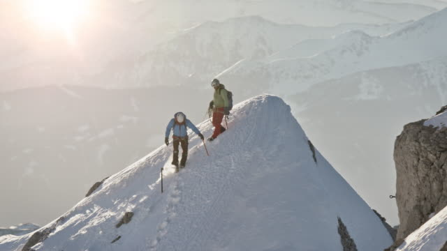 males moving downhill from snowcapped mountain - hiking pole stock videos & royalty-free footage