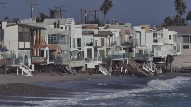 malibu beach houses medium wide establishing shot of expensive ocean front  beach homes along the california ocean  with waves crashing - malibu stock videos & royalty-free footage