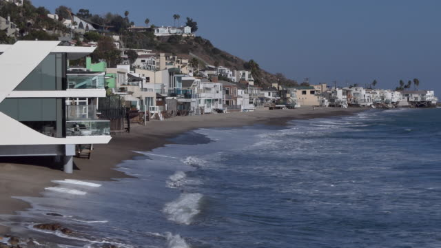 malibu beach houses wide establishing shot of expensive  ocean front beach homes along the california ocean  with waves crashing - malibu stock videos and b-roll footage
