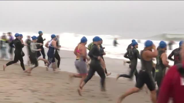 vídeos de stock, filmes e b-roll de malibu, ca, u.s. - people running into water during nautica malibu triathlon on sunday, september 15, 2019. - touca de natação