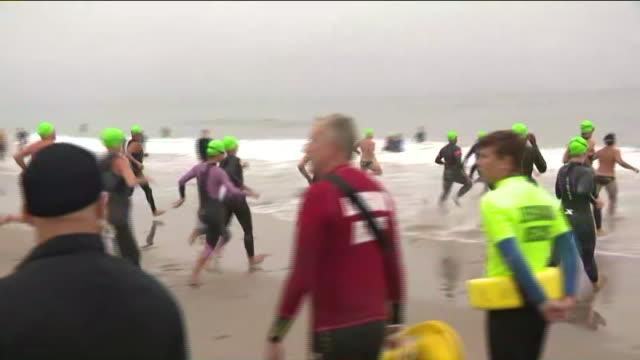 vídeos de stock e filmes b-roll de malibu, ca, u.s. - triathletes running into sea during nautica malibu triathlon, on friday, september 6, 2019. - triatleta
