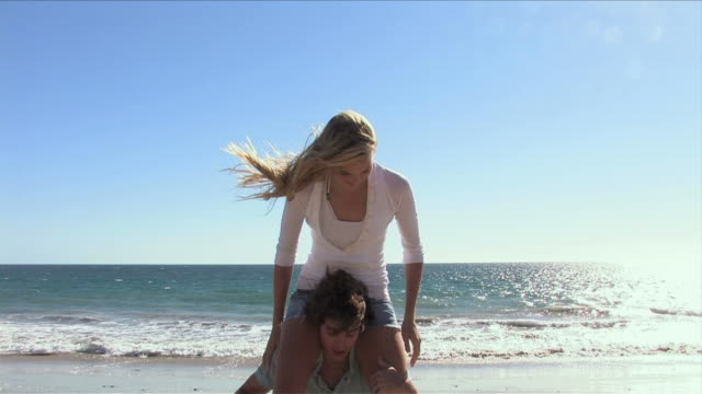 Malibu, California, USAOne young man is putting one woman on his shoulders on the beach